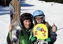 An instructor and child are smiling during snowboarding lessons for kids and adults with experience with skischool Oberharz in Wurmberg.