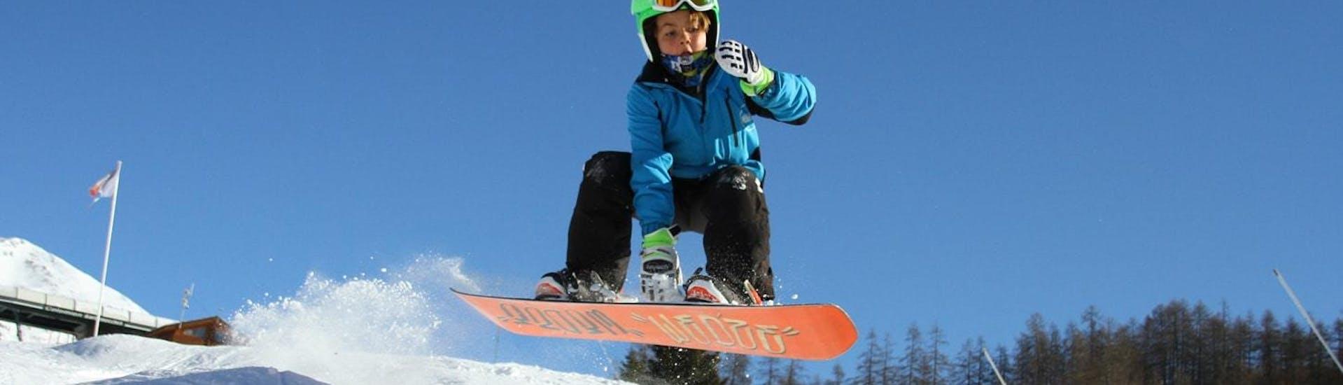 Un jeune snowboardeur tente de nouvelles techniques de freestyle pendant son Cours de snowboard pour Enfants (5-14ans) - Haute-Saison à l'école de ski Scuola di Sci Bardonecchia.
