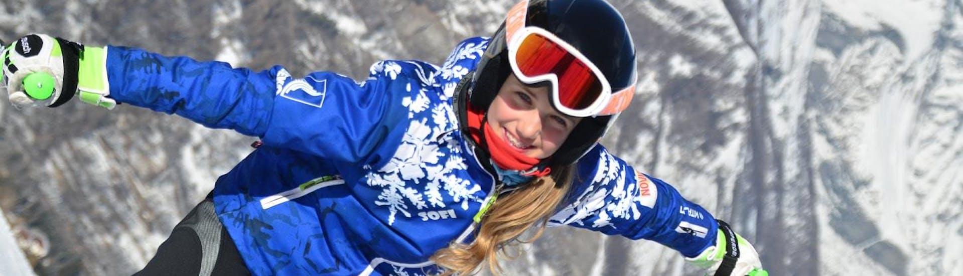 Une jeune fille apprend à faire du snowboard pendant un Cours de snowboard pour Enfants & Adultes - Haute-Saison, sous la supervision d'un moniteur expérimenté de l'école de ski Scuola di Sci Bardonecchia.