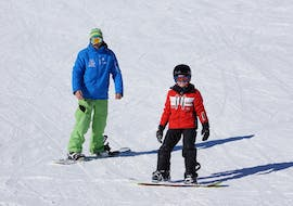 A boy is trying his first turns during some kids snowboarding lessons for all levels with ski school Neustift Olympia at Stubai Glacier.