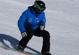 A teenager is improving his use of edges during the snowboarding lessons for teens with ski school Neustift Olympia at Stubai glacier.