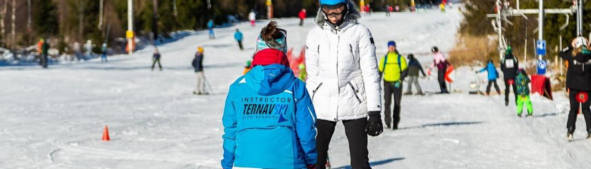 During the Ski Lessons for Adults - Long Lesson - All Levels, an adult is taking the first steps on skis under the supervision of an experienced ski instructor from the ski school Ternavski Snow Academy Tatranska Lomnica.