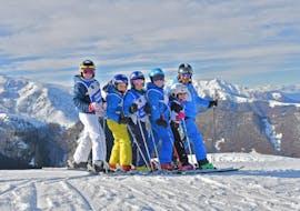 Children and ski instructor have fun during the Kids Ski Lessons (4-12 years) - Christmas of the ski and snowboard school Scuola di Sci e Snowboard Prato Nevoso.