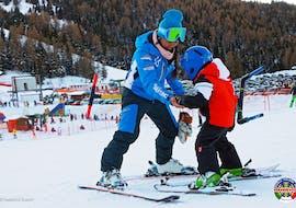 A ski instructor from the ski school Scuola di sci e snowboard Alpe Cimbra teaches a child to ski during Private Ski Lessons for Kids for All Levels.