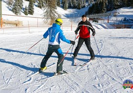 A ski instructor from the ski school Scuola di sci e snowboard Alpe Cimbra and a novice skier during Private Ski Lessons for Adults of All Levels.