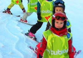 Des enfants skient à la queue-leu-leu pendant leur Cours de ski pour Enfants (3-6 ans) - Vacances avec l'école de ski ESI Font Romeu.
