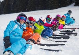 """Des jeunes skieurs sont assis dans la neige entre les monieurs de ski de l'école de ski ESI Font Romeu pendant leur Cours de ski pour Enfants """"Max 6"""" (6-12 ans) - Vacances."""