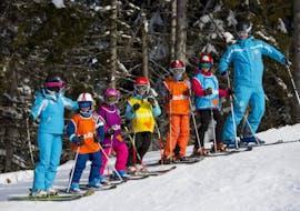 """Des jeunes skieurs se tiennent debout entre les monieurs de ski de l'école de ski ESI Font Romeu pendant leur Cours de ski pour Enfants """"Max 6"""" (6-12 ans) - Basse saison."""