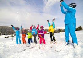 Des jeunes skieurs jettent de la neige dans les airs avec leur moniteur de l'école de ski ESI Font Romeu pendant leur Cours de ski pour Enfants (6-12 ans) - Vacances.