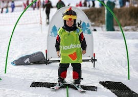 A young child is learning how to ski in the safety of the kindergarten of the ski school Font Romeu during their Private Ski Lessons for Kids - Low Season - All Ages.