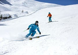 A skier is skiing down a snowy slope behind their ski instructor from the ski school ESI Font Romeu during their Private Ski Lessons for Adults - Holiday - All Levels.
